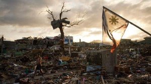 A-man-walks-along-as-the-national-flag-of-the-Philippines-flies-over-the-rubble-of-destroyed-homes-in-Tacloban-AFP